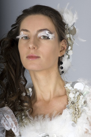 A beautiful young woman in a white dress with ornaments of feathers and makeup on a gray background Banque d'images