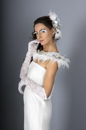 Une belle jeune femme dans une robe blanche avec des ornements de plumes et de maquillage sur un fond gris Banque d'images - 11536693