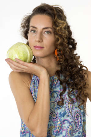 Portrait of a young beautiful woman in a blue dress with an cabbage in his hand