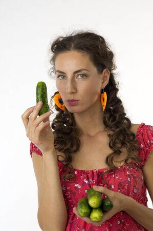 Portrait of a young beautiful woman in a red dress with cucumbers in his hand