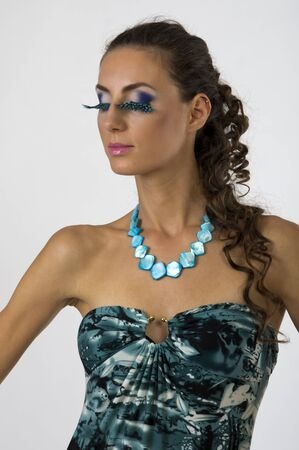 Portrait of a young beautiful woman in a blue dress with bright makeup photo