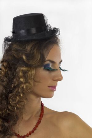 Portrait of a young beautiful woman in a small black cap with bright makeup photo