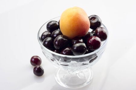 Apricot and cherries on a small vase closeup