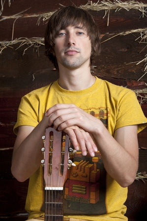 A young man with a guitar against the backdrop of a wooden wall with a straw photo