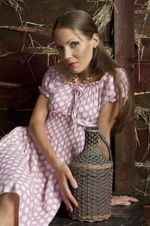 Portrait of an attractive girl in a pink dress with a wooden wall with a straw photo