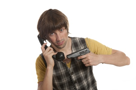 handset: A young man with a handset and a pistol in his hand on a white background Stock Photo