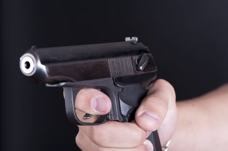 Old pistol in a male hand on black background closeup Stock Photo