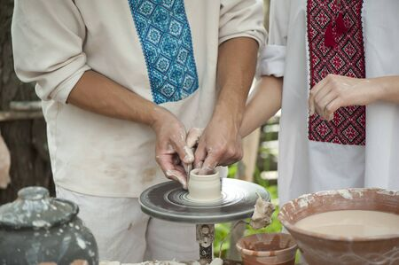 potters wheel: Master Potter teaches young woman working on a Potters wheel Stock Photo