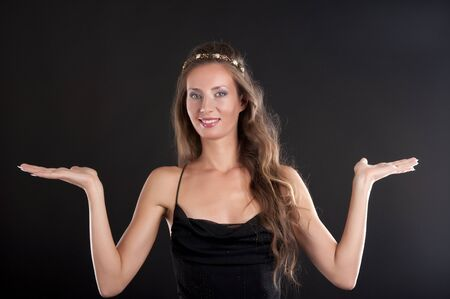 Jonge mooie vrouw in zwarte kleding op een zwarte achtergrond in de studio Stockfoto