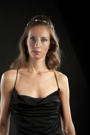 Portrait of a young beautiful woman in a black dress on a black background in the studio Stockfoto