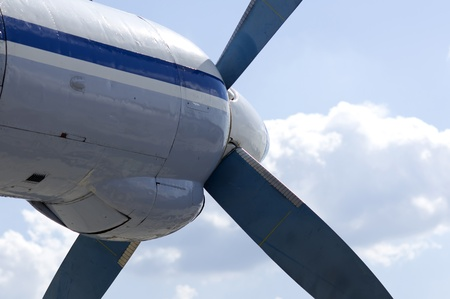 Turboprop transport aircraft against the blue sky closeup photo