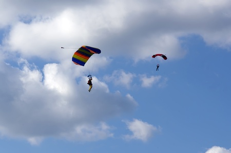 Skydivers with parachute against the blue sky with clouds photo