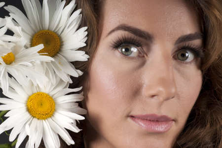 Portrait of a beautiful girl with daisies on a black background in the studio photo