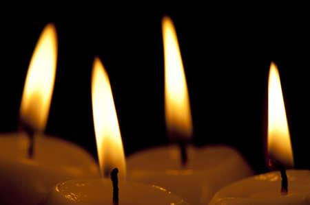 paraffine: Vier uitstekende paraffine kaarsen op een zwarte achtergrond close-up