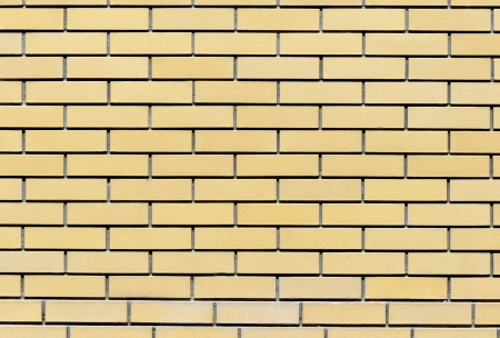 Background of yellow brick wall, illuminated by bright sunlight