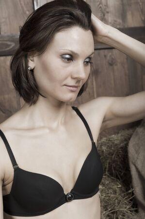Portret van een jonge mooie vrouw in zwarte lingerie op het droge gras Stockfoto