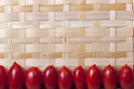 oblong: Small oblong red ripe tomatoes on a wicker wooden platter Stock Photo