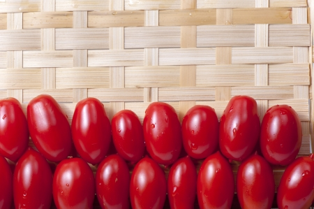 the oblong: Small oblong red ripe tomatoes on a wicker wooden platter Stock Photo