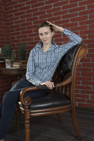 Girl in a blue shirt and jeans to leather chair against a background of red brick wall