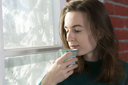 Young woman with a cup of tea by the winter window