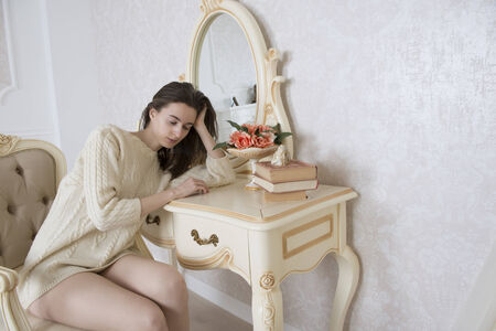 The young woman fell asleep at the table in front of the mirror Stock Photo