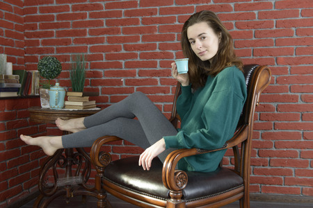 brooding: Young woman in a leather armchair with a cup against the red brick wall Stock Photo