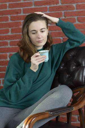 Young woman in a leather armchair with a cup against the red brick wall Banco de Imagens
