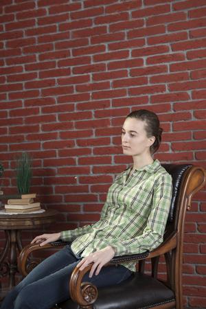 Meisje in een groen shirt en jeans te leren stoel tegen een achtergrond van rode bakstenen muur