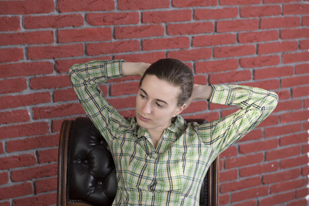 Girl in a green shirt and jeans to leather chair  Banco de Imagens