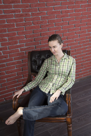 Girl in a green shirt and jeans to leather chair against a background of red brick wall Banco de Imagens