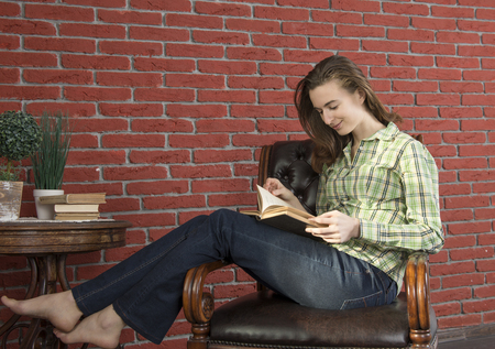 Girl with a book in your hands in a green shirt and jeans to leather chair against a background of red brick wall