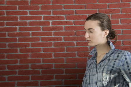 Girl in a blue shirt against a background of red brick wall