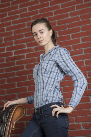 Girl in a blue shirt and jeans against a background of red brick wall Banco de Imagens