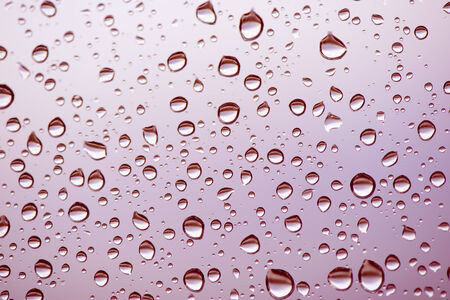 condensation: Different sized raindrops on glass close up