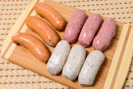 Different meat sausages on a wooden plank closeup Stock Photo