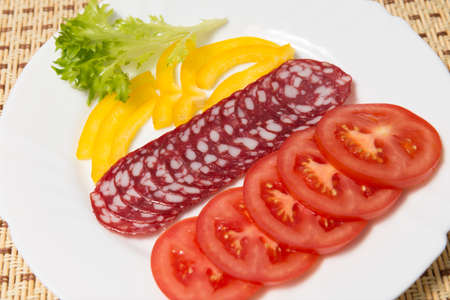 veal sausage: Dry salami and tomatoes on a white plate, closeup