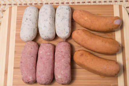 veal sausage: Different meat sausages on a wooden plank closeup Stock Photo