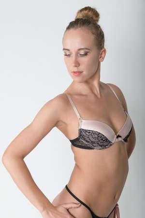 junge nackte m�dchen: Junge sch�ne schlanke Frau in der erotischen schwarzen Dessous auf einem wei�en Hintergrund Lizenzfreie Bilder