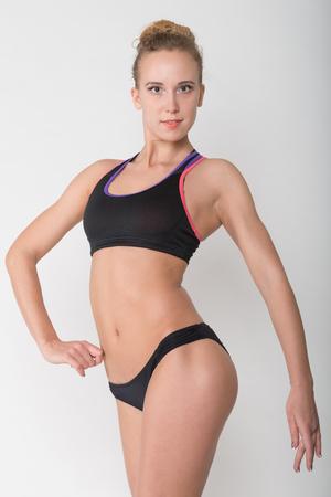 gymnastik: Eine junge Blondine in einem Fitness-Studio für Sport oben auf einem hellen Hintergrund