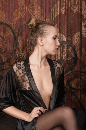 negligee: A young blonde in a black negligee on a red background, profile