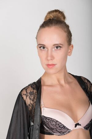 negligee: A young blonde in a black negligee on a gray background