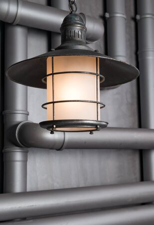 Suspended lighting the lamp shines on the background of water pipes in the wall