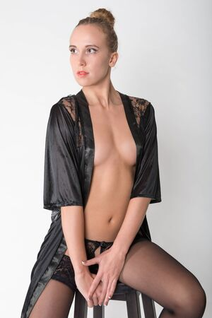 negligee: A young blonde in a black negligee on a gray background, profile, eyes closed