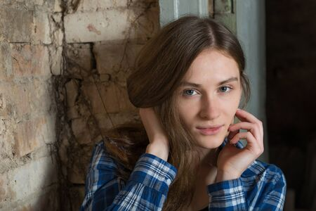 calm woman: Cute young woman in a blue plaid shirt on the background of an old brick wall