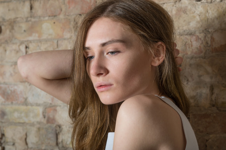 beautiful sad: Young woman with brown hair in a white shirt on the background of an old brick wall