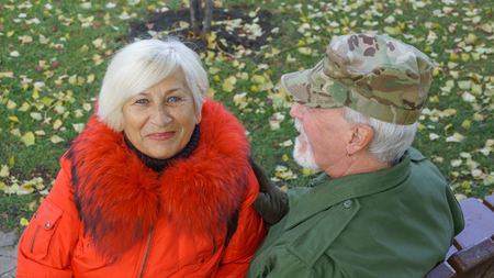 Portrait of a loving elderly couple in the background of the autumn city park
