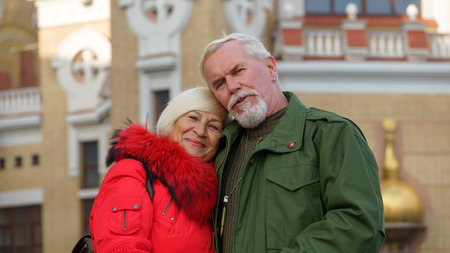 Portrait of a loving elderly couple on a background of autumn cityscape