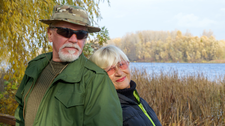 Portrait of a loving elderly couple on a background of autumn landscape on the river bank Stock Photo