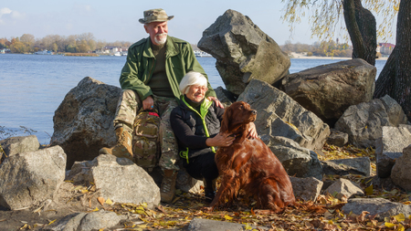 Portrait of a loving elderly couple on a background of autumn landscape on the river bank with a dog setter