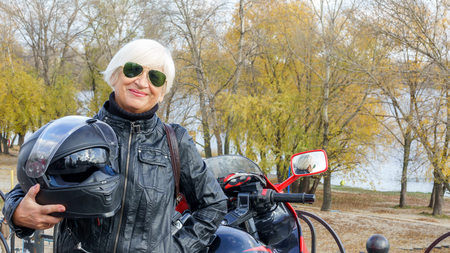 Portrait of a cheerful elderly woman with a motorcycle on the background of an autumn landscape Banco de Imagens